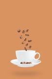 Vliegende koffiebonen en koffiekop Royalty-vrije Stock Fotografie