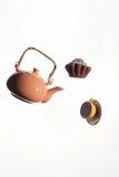 Vliegende theepot, cake, kop op een witte achtergrond Stock Afbeelding