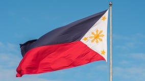 Vliegende tweekleurige vlag van de Filippijnen met centrale gouden zon die de provincies en de sterren vertegenwoordigen de eilan stock fotografie