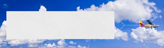 Vliegende vliegtuig en banner stock foto
