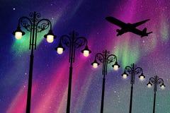 Vliegende vliegtuigen en uitstekende lantaarnpalen bij nacht Royalty-vrije Stock Foto