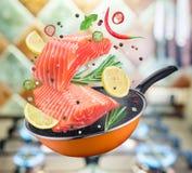 Vliegende zalmlapje vlees en kruiden die in een pan vallen flying stock foto's