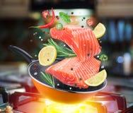 Vliegende zalmlapje vlees en kruiden die in een pan vallen flying stock fotografie