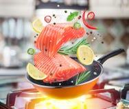 Vliegende zalmlapje vlees en kruiden die in een pan vallen Het vliegen motieeffect van het koken procédé stock fotografie