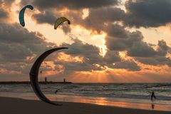 Vlieger die in de zonsondergang bij Nederlands strand surfen Stock Afbeeldingen