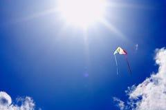 Vlieger die in zonovergoten hemel vliegt Royalty-vrije Stock Afbeeldingen