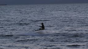 Vlieger-surft tegen een mooie zonsondergang Silhouet van kitesurfer Vakantie op aard Artistiek beeld stock video