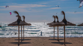 Vliegersurfers in sterk wind, backlight en stro parasols op het strand. royalty-vrije stock foto