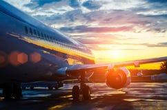 Vliegtuig bij de luchthaven bij dageraad in de zon die van hemelwolken wordt geparkeerd royalty-vrije stock afbeelding