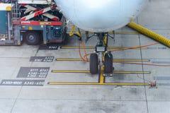 Vliegtuig dat bij luchthaventerminal wordt die door grondbemanning wordt onderhouden geparkeerd die voor een vlucht voorbereiding royalty-vrije stock foto's