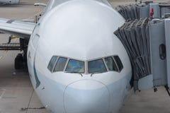 Vliegtuig dat bij luchthaventerminal wordt die door grondbemanning wordt onderhouden geparkeerd die voor een vlucht voorbereiding stock foto's