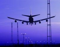 Vliegtuig dat bij schemer landt Stock Foto's