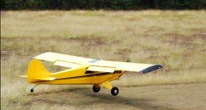 Vliegtuig dat in gras landt Stock Afbeelding