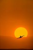 Vliegtuig dat met heldere oranje zonsopgang neemt Royalty-vrije Stock Foto's