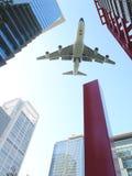 Vliegtuig dat over stad vliegt Stock Foto