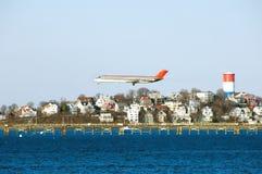 Vliegtuig dat voor het landen bij Logan luchthaven voorbereidingen treft. Stock Fotografie