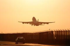 Vliegtuig dat in Zonsondergang van start gaat Stock Afbeelding