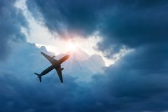 Vliegtuig in de donkerblauwe hemel en wolk in zonnestraal royalty-vrije stock fotografie