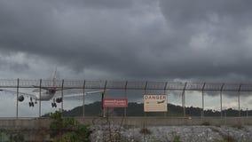 Vliegtuig die bij de luchthaven en het waarschuwingsbord op de omheining over bewolkte hemel landen stock video