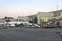 Vliegtuig die bij de vinger in de terminal aankomen stock fotografie