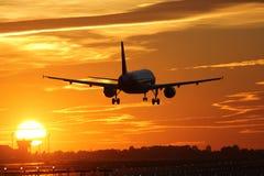 Vliegtuig die bij een luchthaven tijdens zonsondergang landen Stock Foto's