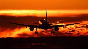 Vliegtuig die bij Otopeni luchthaven tijdens zonsondergang met rode hemel bevlekken Royalty-vrije Stock Foto's