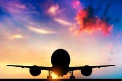 Vliegtuig die bij zonsondergang opstijgen stock fotografie