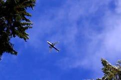Vliegtuig die in blauwe hemel met wolken vliegen Stock Fotografie