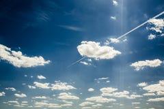 Vliegtuig die in de blauwe hemel onder wolken en zonlicht vliegen Royalty-vrije Stock Afbeeldingen