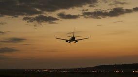 Vliegtuig die in een zonsondergang landen Stock Afbeeldingen