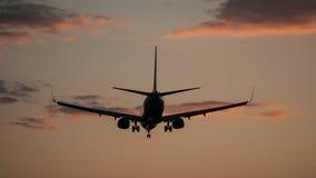 Vliegtuig die in een zonsondergang landen Royalty-vrije Stock Foto