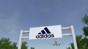 Vliegtuig die over de reclame van aanplakbord met de inschrijving en het embleem van Adidas vliegen Redactie 3D het teruggeven 4K stock video