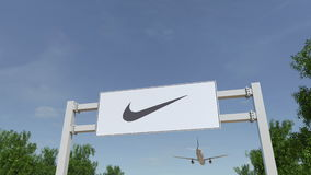 Vliegtuig die over de reclame van aanplakbord met de inschrijving en het embleem van Nike vliegen Het redactie 3D teruggeven Stock Foto