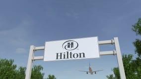 Vliegtuig die over de reclame van aanplakbord met Hilton Hotels Resorts-embleem vliegen Het redactie 3D teruggeven Stock Afbeelding