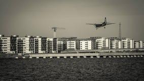 Vliegtuig die over gebouwen en water vliegen Tref voor het landen voorbereidingen stock afbeeldingen