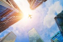 Vliegtuig die over moderne bedrijfswolkenkrabbers vliegen Vervoer, reis Royalty-vrije Stock Foto's