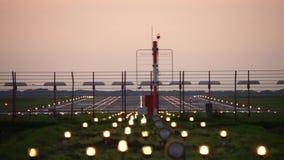 Vliegtuig die in silhouet tegen een oranje zonsonderganghemel landen stock footage