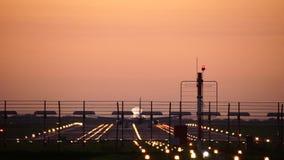 Vliegtuig die in silhouet tegen een oranje zonsonderganghemel landen stock videobeelden