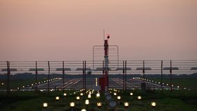 Vliegtuig die in silhouet tegen een oranje zonsonderganghemel landen stock video