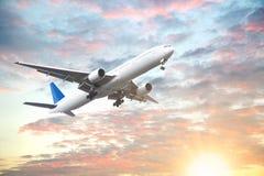 Vliegtuig die in zonsonderganghemel vliegen met mooie wolk Royalty-vrije Stock Afbeeldingen