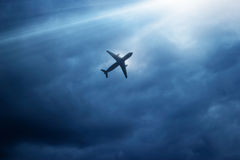 Vliegtuig in donkerblauwe hemel en wolk in strom Stock Foto's