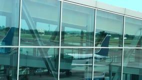 Vliegtuig door het inschepen gang wordt en luchthavengebied in eindvensters wordt weerspiegeld geparkeerd dat stock video