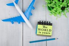 vliegtuig en notastootkussen met tekst & x22; De wereld is yours& x22; op witte houten lijst stock foto's