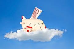 Vliegtuig gevormd spaarvarken op een wolk met bankbiljet stock afbeeldingen