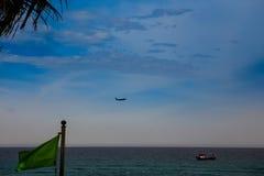 vliegtuig in hemel boven overzeese vissersboot groene banner op voorgrond Stock Fotografie