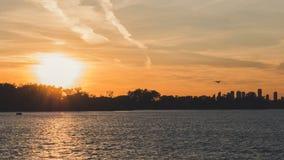 Vliegtuig het vastspijkeren weg in zonsondergang met meer vooraan mooie scène met zachte oranje kleurenachtergrond royalty-vrije stock foto's
