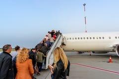 Vliegtuig in luchthaven klaar aan het vliegen en mensen het uitgaan stock fotografie