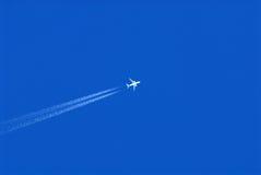 Vliegtuig met dampslepen in een blauwe hemel Stock Fotografie