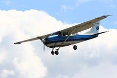 Vliegtuig naderbij komen die na het laten vallen van groep skydivers landen Stock Foto's