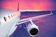 Vliegtuig op baan bij zonsondergang stock foto